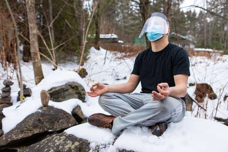 Funny shot of a young man in a t-shirt sitting in the yoga lotus flower position on a big rock in the snow, wearing covid mask and protective visor.