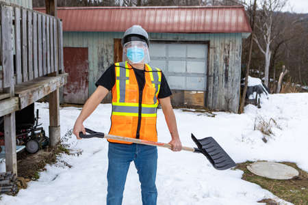Medium full shot of a man wearing a fluo visibility jacket over a t-shirt, protective face mask and plastic visor, standing in the snow with a shovel