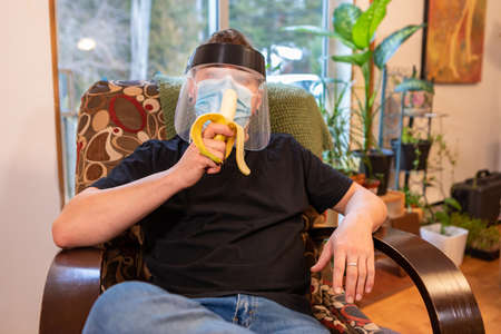Medium close shot of a young man relaxing in an armchair indoor and eating a banana, wearing protective face mask and anti covid plastic visor.