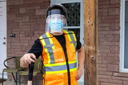 Medium close shot of a man wearing an orange fluo visibility jacket, covid protective face mask and plastic visor leaning on the handle of a shovel