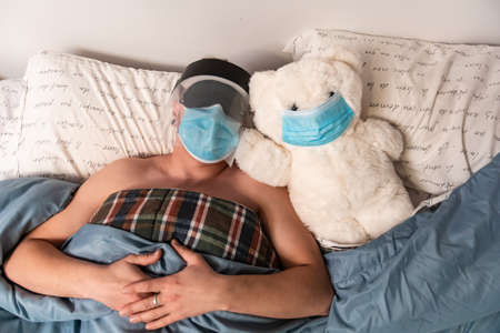 A man and a big white teddy bear in bed, both wearing coronavirus protective mask. Mas also wars sleeping mask and plastic visor. Ironic. 免版税图像
