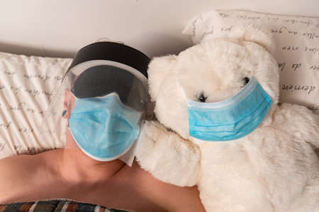 Close up of man and a big white teddy bear in bed, both wearing coronavirus protective mask. Man also wars sleeping mask and plastic visor. Ironic.
