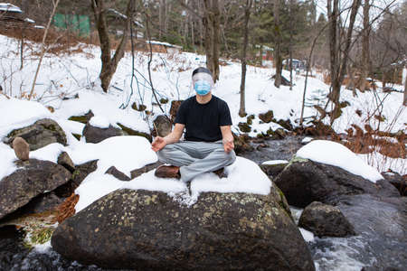 Wide angle shot of man in a t-shirt sitting in the yoga lotus flower position on a big rock in the snow, wearing covid mask and protective visor.