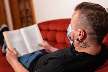 Exaggerated attention to contagion prevention. View from behind of a man reading on a red couch wearing protective sanitary mask against covid.