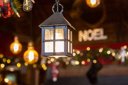 Selective focus of beautiful little hut shaped lamp with illuminated bulb and noel text written in blur background in restaurant