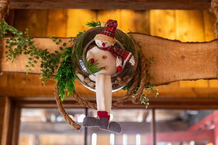 Selective focus of smiling stuffed snowman toy with wreath and leaves on wooden piece used as decoration for christmas and new year in restaurant