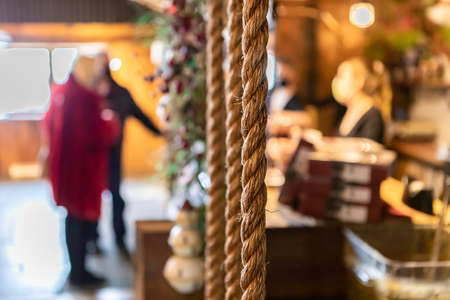 Selective focus of rope hanging from rooftop during christmas in restaurant as decoration with customers at counter purchasing food 写真素材