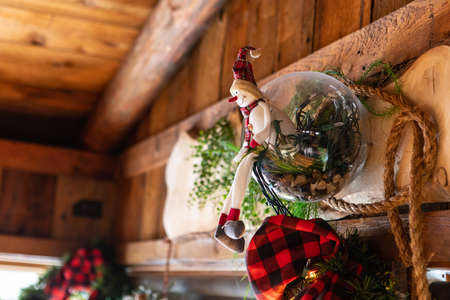 Smiling stuffed snowman toy sitting inside a ball, with wreath and leaves on window frame used as decoration on roof for christmas and new year in restaurant