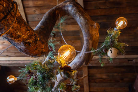 Selective focus of illuminate bulbs and fir branches and pine cones and christmas ornaments over atypical tree tree tronk in restaurant