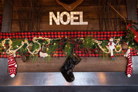 Beautiful decoration of leaves with lightening and cherries over red lace with stockings and pine leaves with noel text with illuminated bulbs