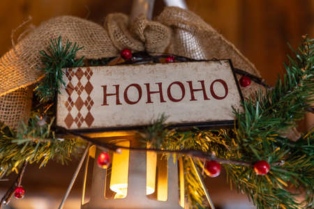 Selective focus of wooden plank with text written as hohoho for santa decorated with decoration of christmas tree leaves over bulb in restaurant