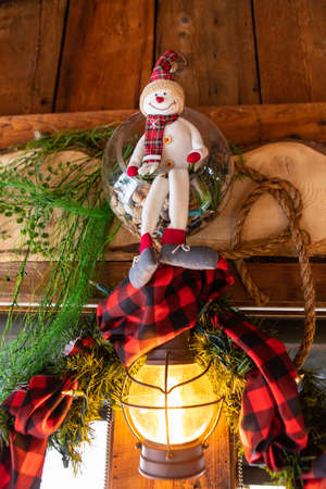 Smiling stuffed snoman toy sitting inside a ball, with wreath and leaves on wooden piece used as decoration over bulb for christmas and new year in restaurant