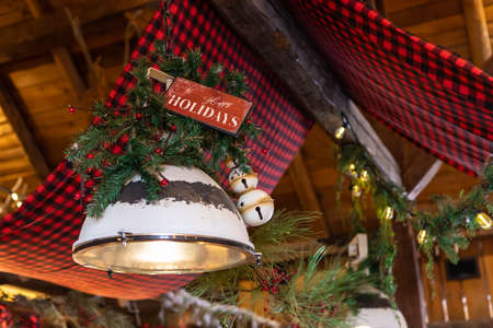 Wooden plank with text written as happy holidays decorated with decoration of pine leaves and christmas ornaments over bulb in restaurant 写真素材