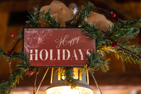 Selective focus of wooden plank with text written as happy holidays decorated with decoration of pine leaves over bulb in restaurant