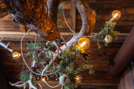 Low angle view of illuminate bulbs and fir branches with pinecones and christmas ornaments over circular tree tronk as decoration in restaurant