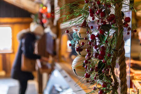Selective focus of pine and fir needles with cherries and ornaments hanging in restaurant with woman in winter clothing decorating place during christmas
