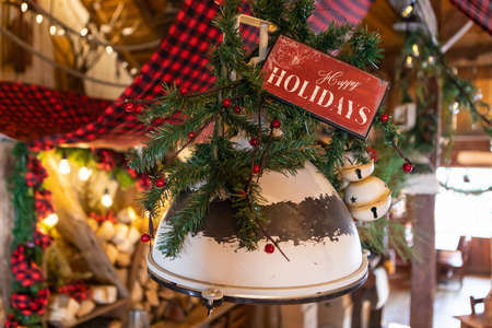 Selective focus of wooden plank with text written as happy holidays decorated with decoration of pine leaves and christmas ornaments over bulb in restaurant