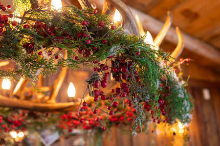 Selective focus of christmas decoration with fir branches and cherries, reindeer horns as luminary structure over with illuminated bulbs inside a restaurant