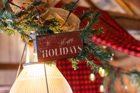 Selective focus of wooden plank with text written as happy holidays decorated with decoration of fir branches and christmas ornaments over bulb in restaurant