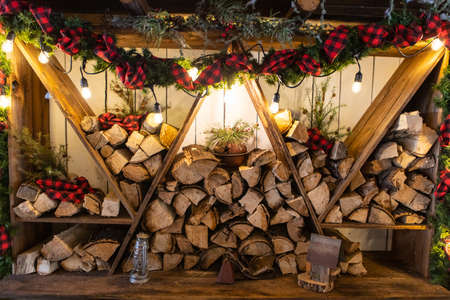 Multiple wooden logs stacked in triangular shelves with illuminated bulbs and top decorated with ribbons and lighting outside restaurant