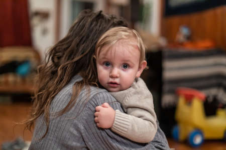 Cute little baby boy with blue eyes and blond hair looking at camera over moms shoulder while in moms arms. Intimate cuddles between mother and son. 写真素材