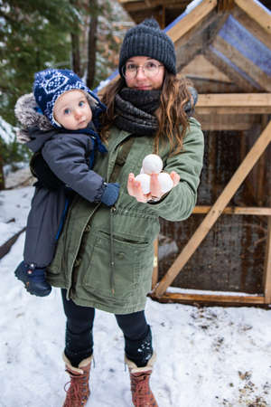 Babys first nature exploration with mom. Mom holding baby in one arm and a handful of organic eggs coming from a chicken coop in the other hand.