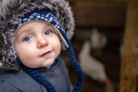 Close up of a cute baby boy with angel face and smart look dressed in winter suit with fur hood. In the background a chicken coop with white hens. 写真素材
