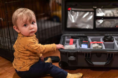 Cute little baby boy looking at camera while touching his fathers suitcase filled with professional video equipment. Curiosity and discovery concept. 写真素材
