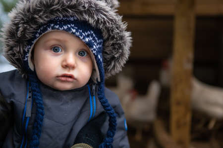 Close up of a cute baby boy with angel face and blue eyes dressed in winter suit with furry hood. In the background, a chicken coop with white hens.