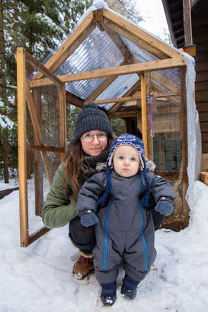 Mom and toddler posing for camera kneeling in the snow during the exploration of a chicken coop in the snow. Babys first discoveries.