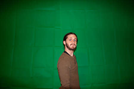 Shot of a young man with a beard, posing with eyes fully opened, and a pout, with a poorly lit greenscreen as background, taken in Montreal