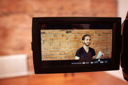 Behind the scene picture of a young man, recording a video with papers in hand, the picture includes video camera and a brick wall background 写真素材
