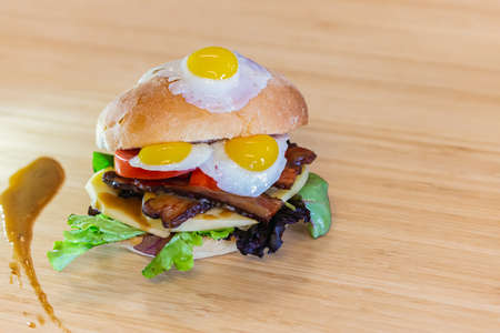Full picture of a fully stuffed quail egg sandwich, layered with cheese and vegetables, placed neatly on a wooden kitchen shelf 写真素材