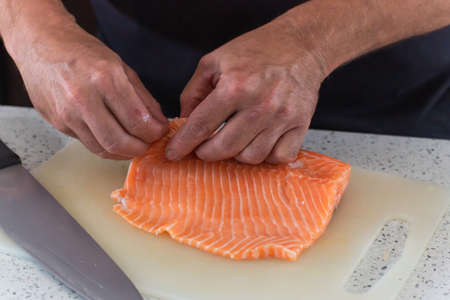Close up shot of a raw salmon, half held between two hands, with rest of it placed on a cutting board, big knife is placed on its left side.