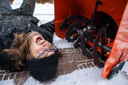 Close up shot of a man lying in the snow in front of a snowplough, making funny faces with a crazy look. Fooling around while cleaning a country road 写真素材
