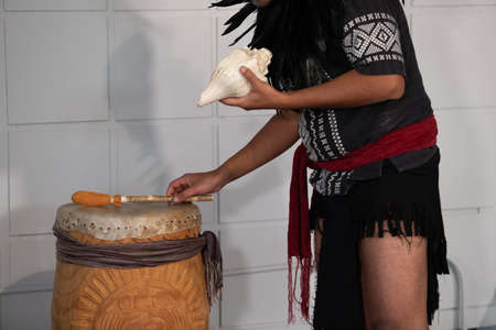 Moments from a native drum workshop. Man with traditional native or indian decorations made with feathers holding a shell in front of a congas drum.