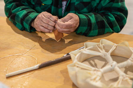 Close up of mans hands roughly sewing a piece of leather to create the soft head of a drum stick, during a native drum workshop.