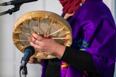 Sound demonstration during a native drum workshop. Woman in colored native scarf holing a sand made drum in front of a microphone, ready to perform.