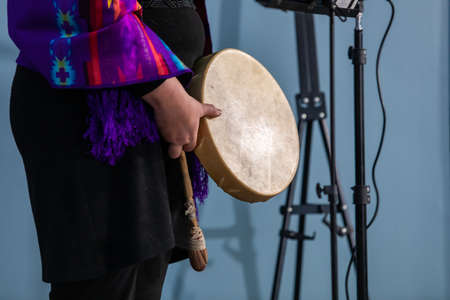 Sound demonstration during a native drum workshop. Woman in colored native scarf holing a sand made drum and a stick in front of a microphone.
