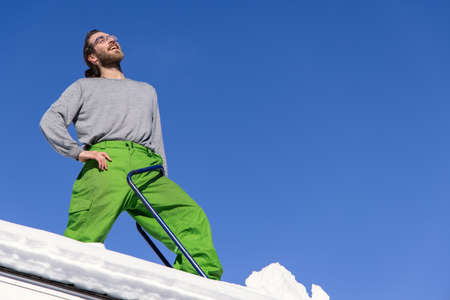 Funny portrait from below of a young man standing on the roof of a house, arm on his hip and blue shovel at his side, during a snow removal operation