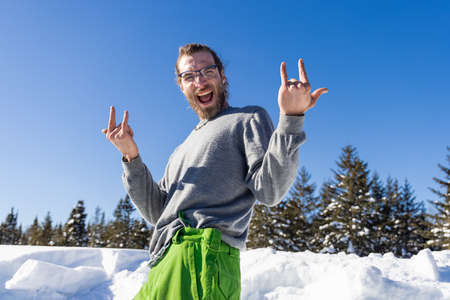 Iconic, ironic portrait of a young snow remover posing for camera with a big grin and a and devils horns gesture during a break in the job. Standard-Bild