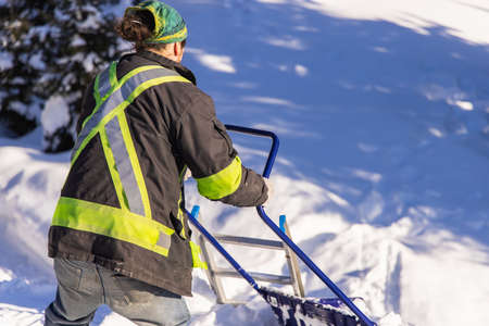 Rear view of a young man in visibility jacket and blue manual shovel removing knee deep fresh snow from a country house during a sunny winter day.