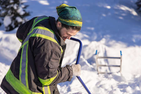Young man in fluo visibility clothes and blue manual shovel removing knee deep fresh snow from a country house in canada during a sunny winter day.