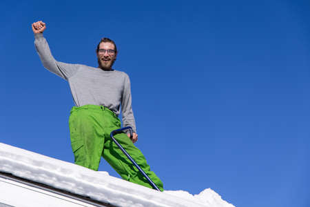 Funny portrait from below of a young man standing on the roof of a house with his arm raised and a blue shovel, during a snow removal operation. Standard-Bild