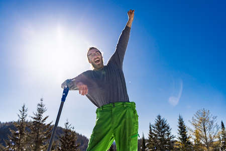 Funny, arm up portrait of a smiling man leaning on the handle of a blue snow shovel while taking a break during a snow removal job. Sunny winter day Standard-Bild