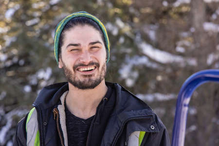 Close up portrait of a smiling young bearded man in posing for camera during a break ina fresh snow removal job in a canadian house.