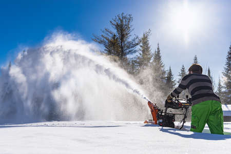Wide angle view from behind of a man maneuvering a snowplough in the knee deep fresh snow, with a high jet exiting the machine like a snowstorm