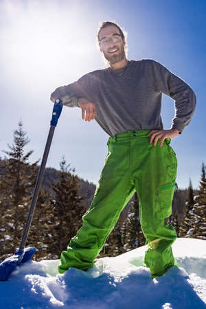 Full figure portrait of a smiling man leaning on the handle of a blue snow shovel while taking a break during a snow removal job in a country house.