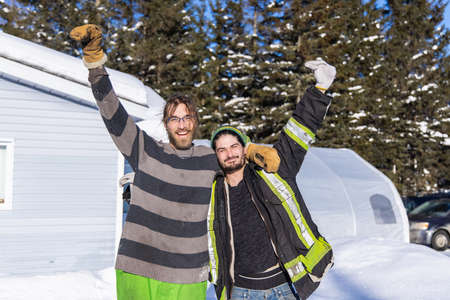 Portrait of two smiling, good willing young men posing for camera with arms up after a hard day of snow removing in a canadian country house.