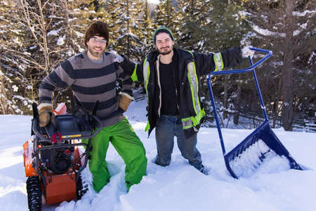 Portrait of two young men posing for camera with their snow removing tools, a bright orange mechanical snowplough and a blue manual shovel.